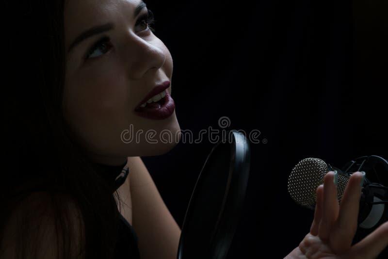 Muchacha hermosa que canta en el estudio de grabación con el micrófono imagen de archivo