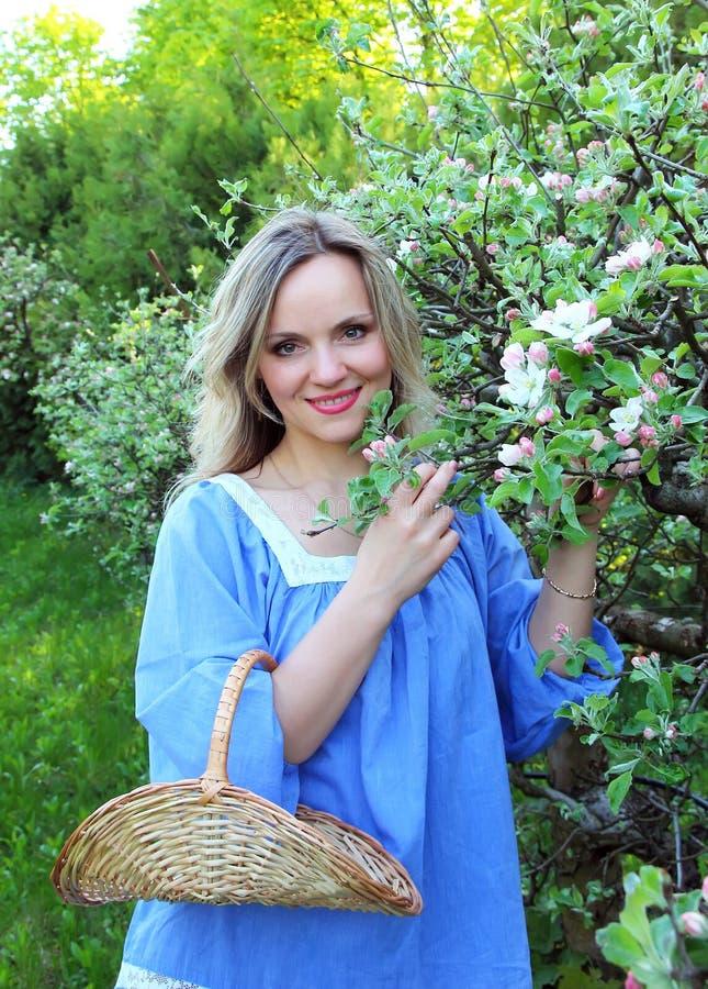 Muchacha hermosa que coloca el manzano cercano fotografía de archivo