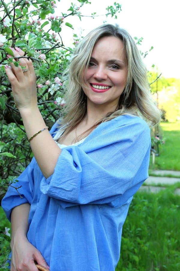 Muchacha hermosa que coloca el manzano cercano fotos de archivo libres de regalías