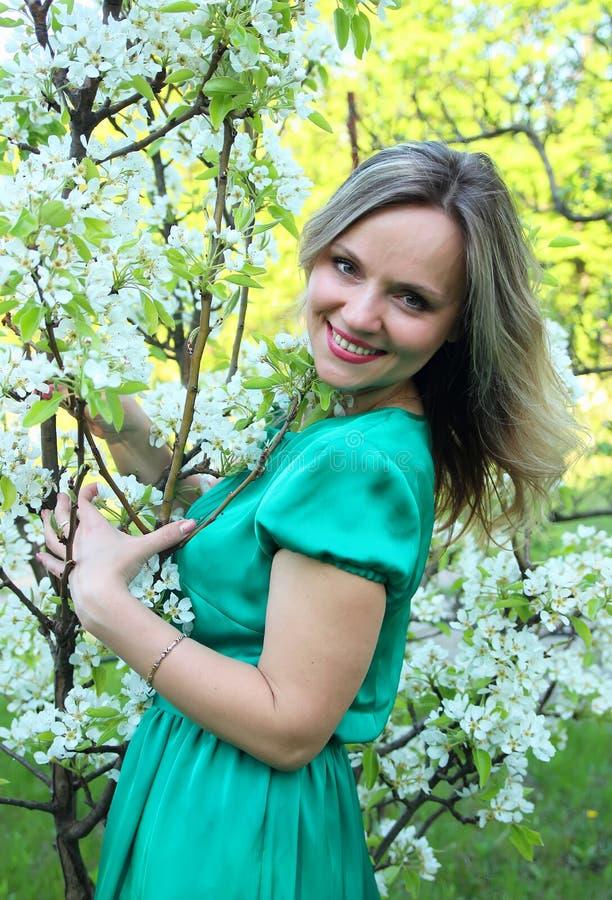 Muchacha hermosa que coloca el manzano cercano fotos de archivo