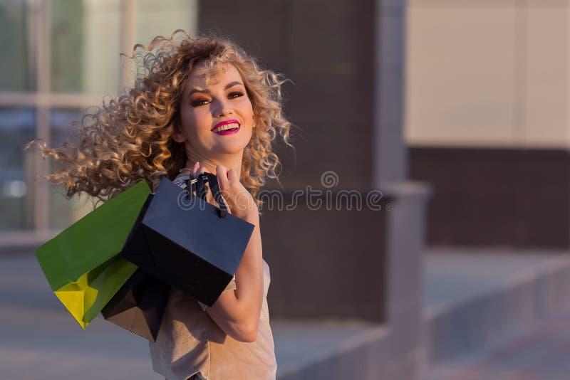 Muchacha hermosa que da vuelta alrededor con los panieres y que sonríe en cámara Mujer joven que camina después de venta de la al foto de archivo