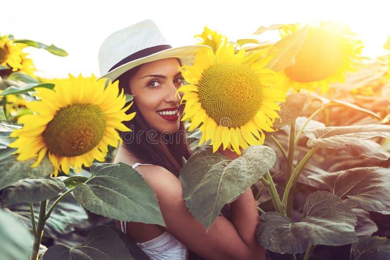 Muchacha hermosa que disfruta de la naturaleza en el campo de girasoles en la puesta del sol imagen de archivo