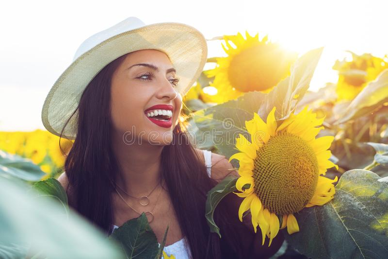Muchacha hermosa que disfruta de la naturaleza en el campo de girasoles en la puesta del sol foto de archivo libre de regalías