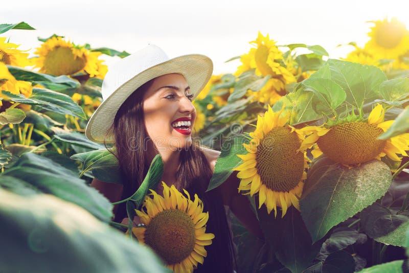 Muchacha hermosa que disfruta de la naturaleza en el campo de girasoles en la puesta del sol fotografía de archivo libre de regalías