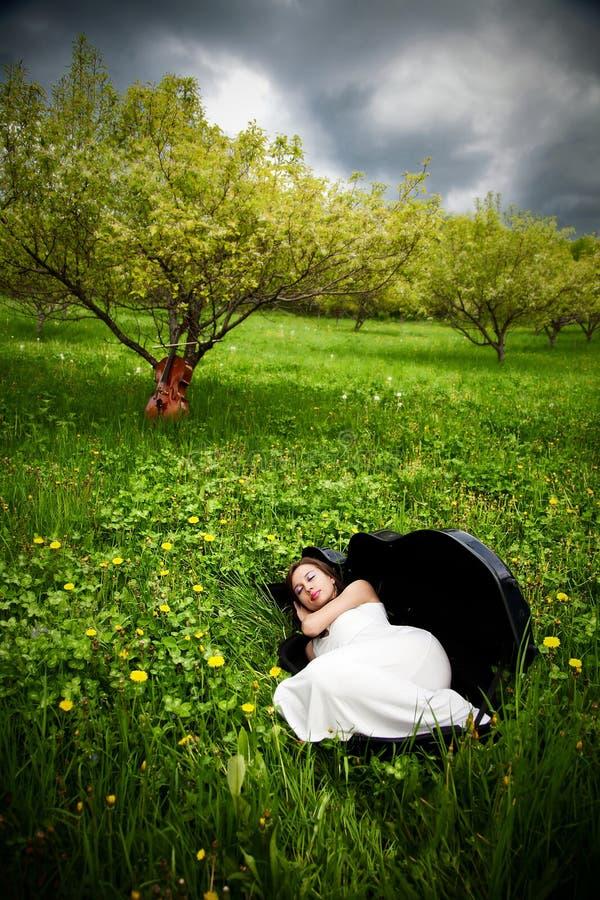 Muchacha hermosa que duerme en caso del violoncelo fotos de archivo libres de regalías