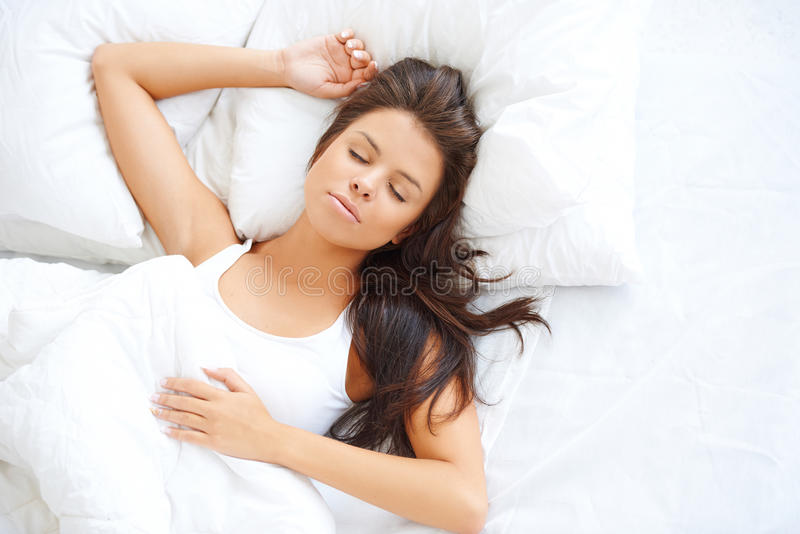 Muchacha hermosa que duerme en el lecho blanco imágenes de archivo libres de regalías