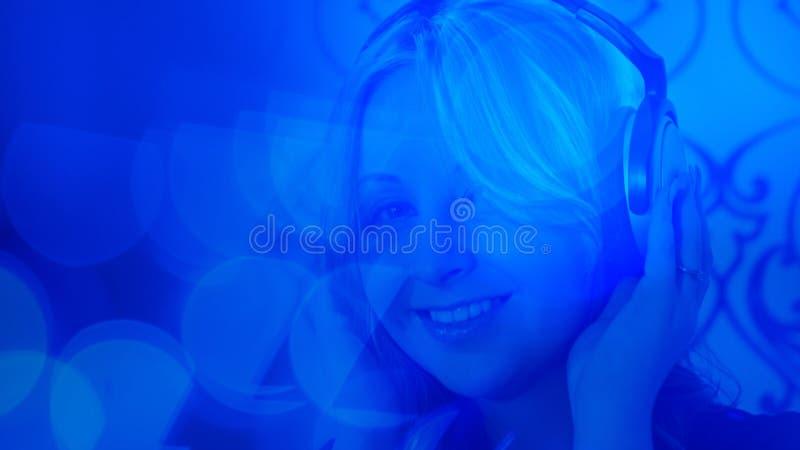 Muchacha hermosa que escucha la música con los auriculares, fondo azul de la luz del bokeh imagen de archivo