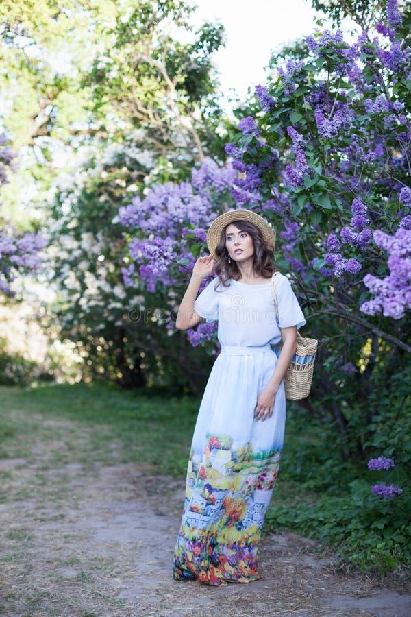Muchacha hermosa que goza del olor de la lila en un día de verano Concepto del Aromatherapy y de la primavera Una muchacha bonita imágenes de archivo libres de regalías