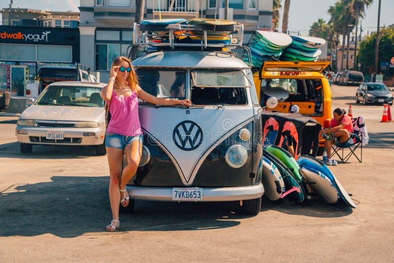 Muchacha hermosa que hace una pausa al hippy de VW foto de archivo
