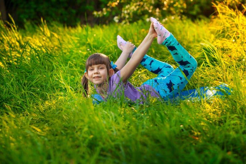 Muchacha hermosa que hace yoga al aire libre en hierba verde foto de archivo libre de regalías