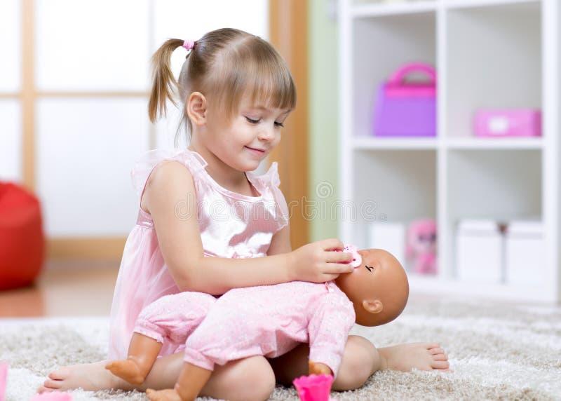 Muchacha hermosa que juega al doctor con una muñeca fotografía de archivo libre de regalías