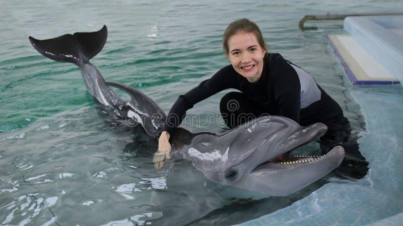 Muchacha hermosa que juega en la piscina con un delfín imagenes de archivo