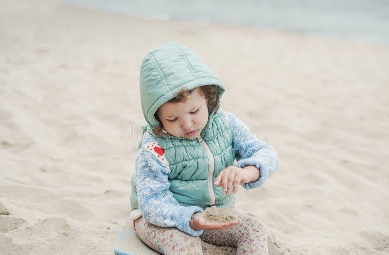 Muchacha hermosa que juega en la playa en el chaleco caliente fotos de archivo