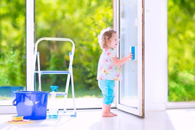 Muchacha hermosa que lava una ventana en el sitio blanco imágenes de archivo libres de regalías