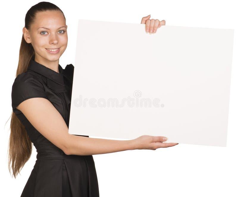 Muchacha hermosa que lleva a cabo el cartel blanco en blanco y foto de archivo