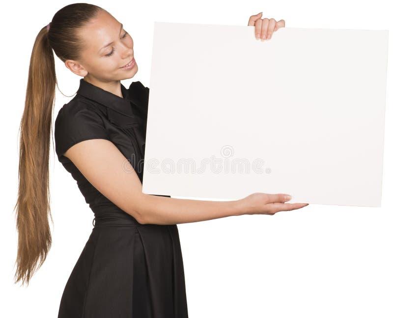 Muchacha hermosa que lleva a cabo el cartel blanco en blanco y foto de archivo libre de regalías