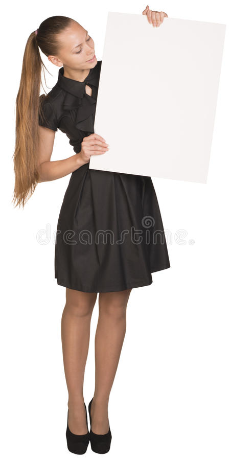 Muchacha hermosa que lleva a cabo el cartel blanco en blanco y fotografía de archivo