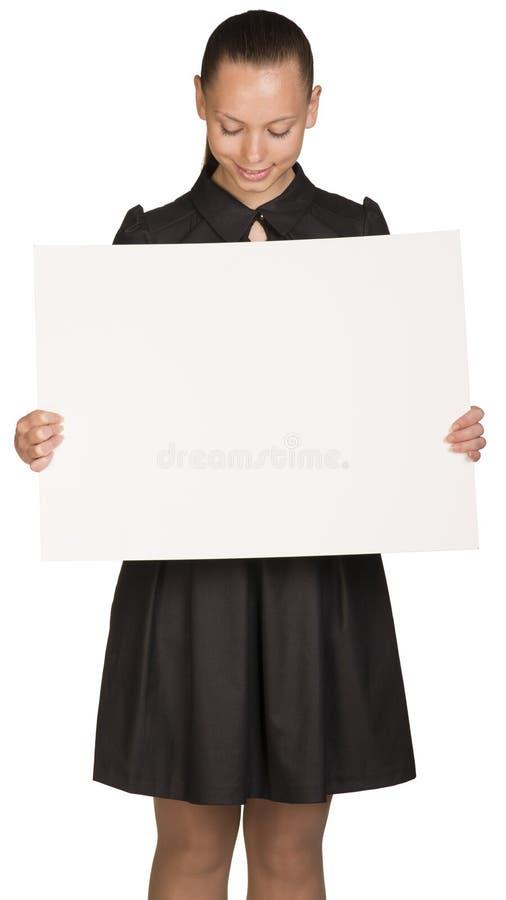 Muchacha hermosa que lleva a cabo el cartel blanco en blanco y fotos de archivo