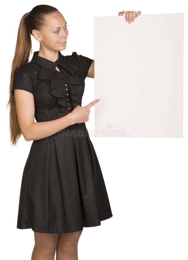 Muchacha hermosa que lleva a cabo el cartel blanco en blanco y imágenes de archivo libres de regalías