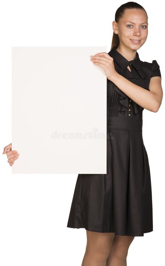 Muchacha hermosa que lleva a cabo el cartel blanco en blanco y fotos de archivo libres de regalías