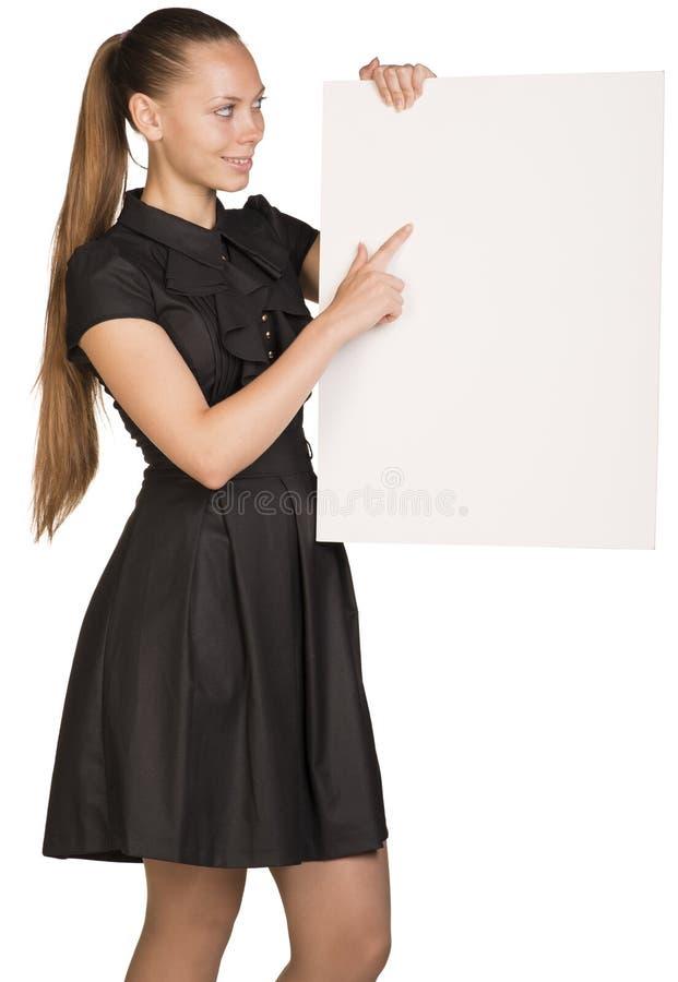 Muchacha hermosa que lleva a cabo el cartel blanco en blanco y fotografía de archivo libre de regalías
