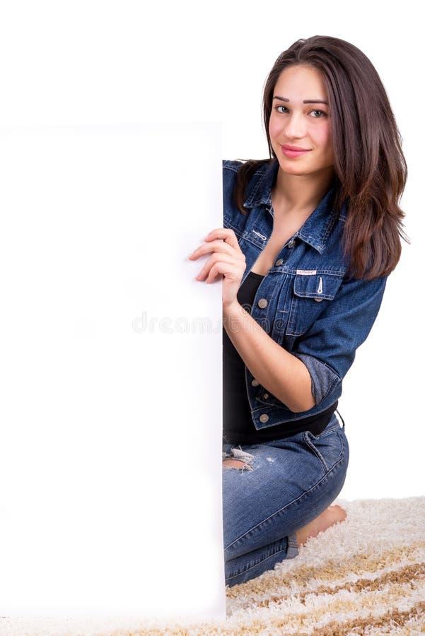 Muchacha hermosa que lleva a cabo un cartel blanco que se sienta en la alfombra fotos de archivo