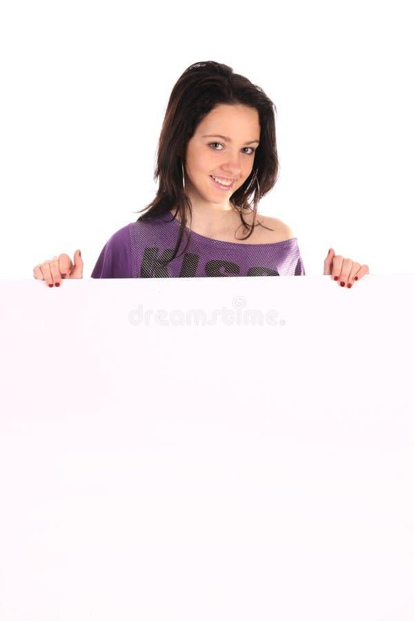 Muchacha hermosa que lleva a cabo un espacio en blanco fotos de archivo libres de regalías