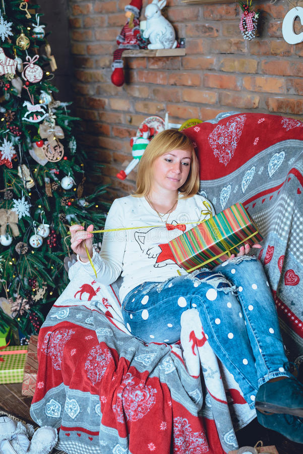 Muchacha hermosa que lleva a cabo un regalo de Navidad delante de ella imagen de archivo