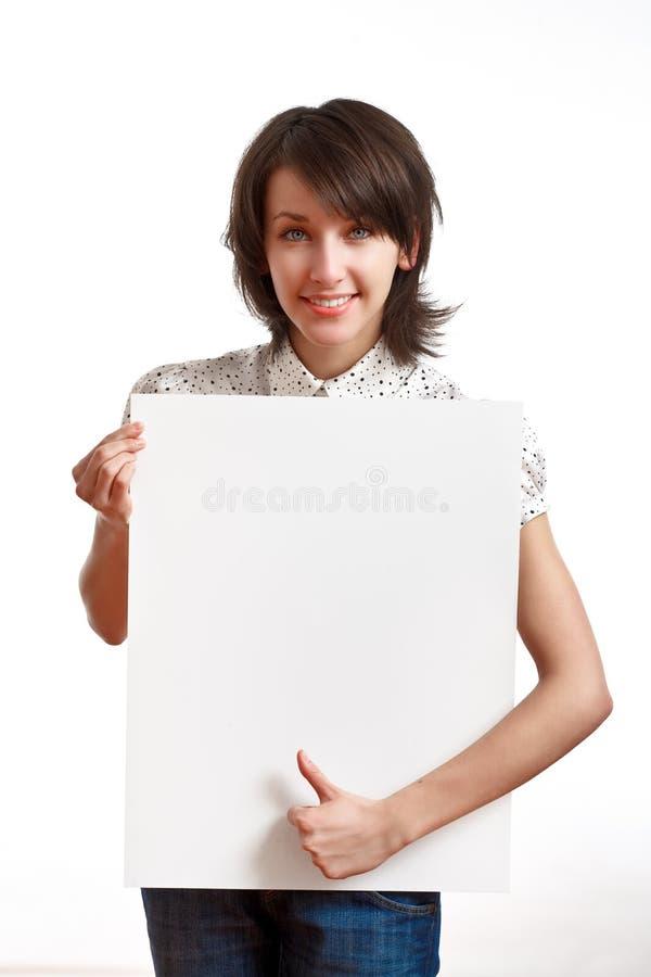 Muchacha hermosa que lleva a cabo a una tarjeta blanca vacía fotografía de archivo