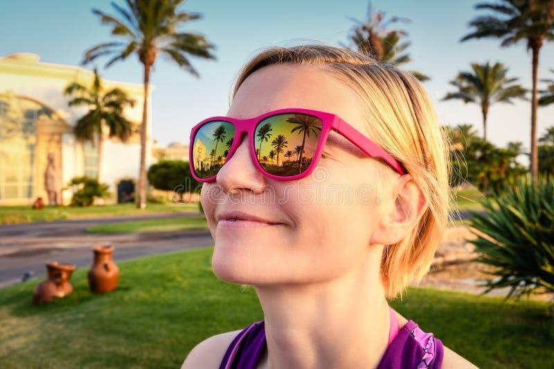 Muchacha hermosa que lleva las gafas de sol rosadas con las palmeras en el fondo imagen de archivo libre de regalías