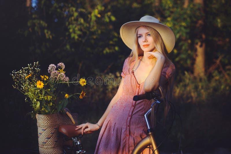 Muchacha hermosa que lleva un vestido rosado agradable que se divierte en un parque con una bicicleta que sostiene una cesta herm imágenes de archivo libres de regalías