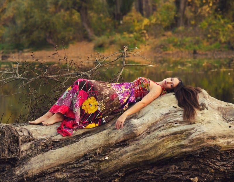 Muchacha hermosa que miente en el tronco de árbol imagen de archivo libre de regalías