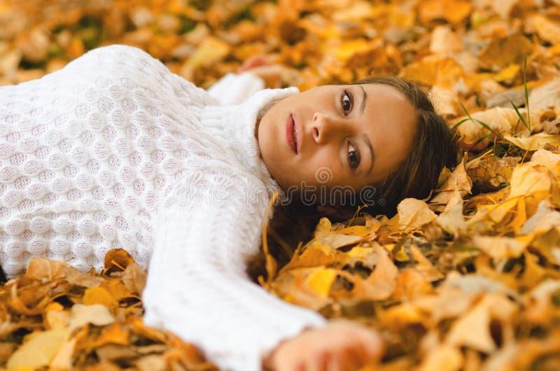 Muchacha hermosa que miente en las hojas de otoño fotos de archivo libres de regalías