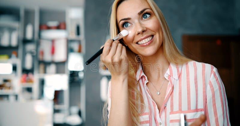 Muchacha hermosa que mira en el espejo y que aplica el cosmético foto de archivo libre de regalías
