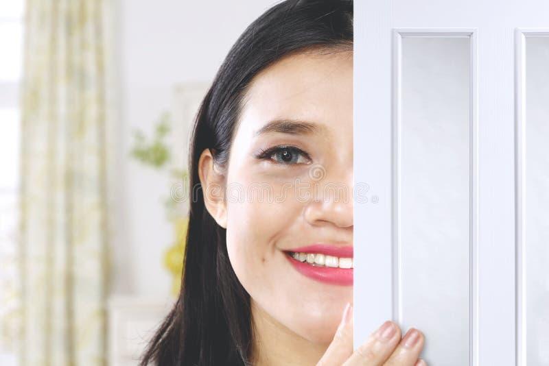 Muchacha hermosa que mira furtivamente detrás de una puerta fotografía de archivo libre de regalías
