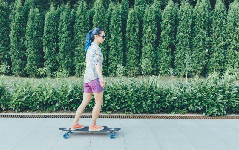 Muchacha hermosa que monta un longboard al aire libre fotos de archivo
