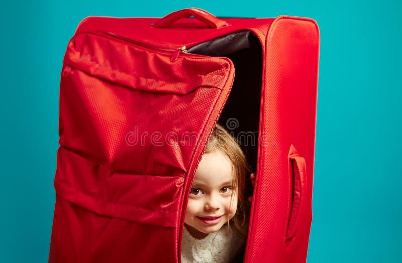 Muchacha hermosa que oculta en el bolso rojo del equipaje, tiro del primer en azul aislado imagenes de archivo