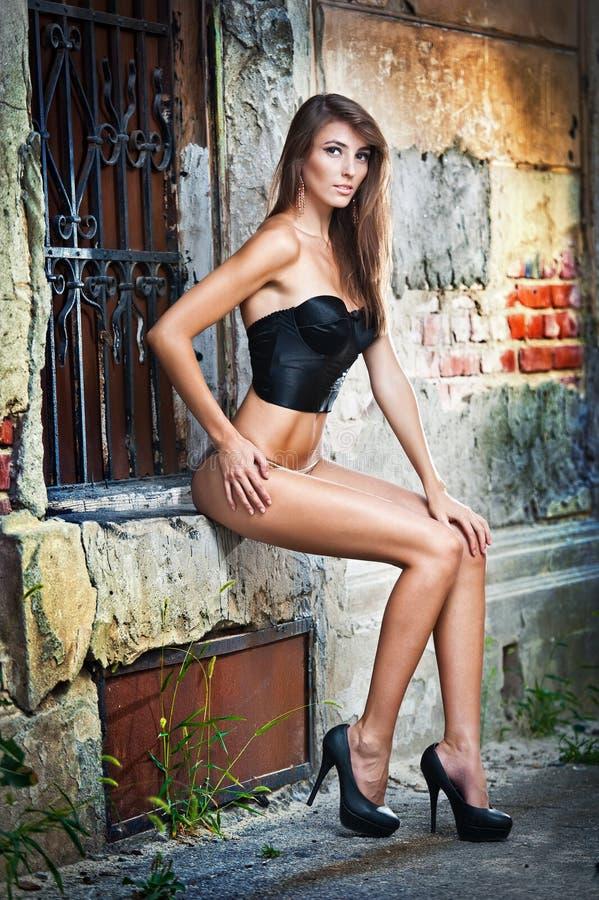 Muchacha hermosa que plantea la manera cerca de la pared de ladrillo roja foto de archivo libre de regalías