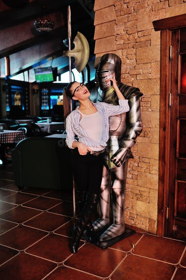 muchacha hermosa que presenta así como caballero medieval en armadura imagenes de archivo