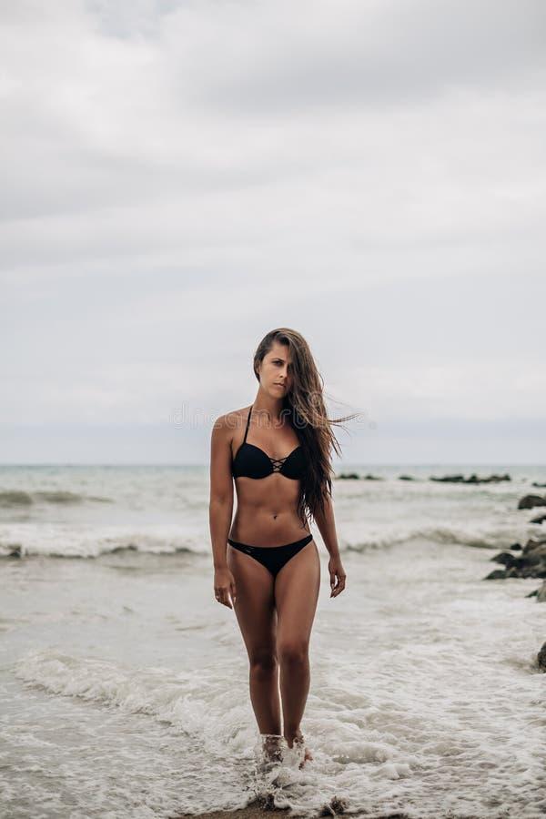 Muchacha hermosa que sale del mar ondulado foto de archivo libre de regalías