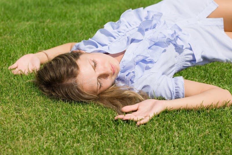 Muchacha hermosa que se acuesta de hierba imagenes de archivo