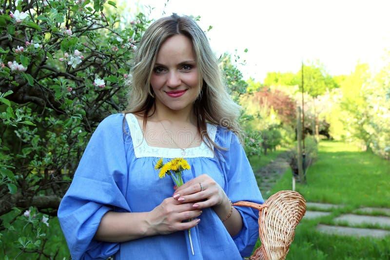 Muchacha hermosa que se coloca en el manzanar foto de archivo