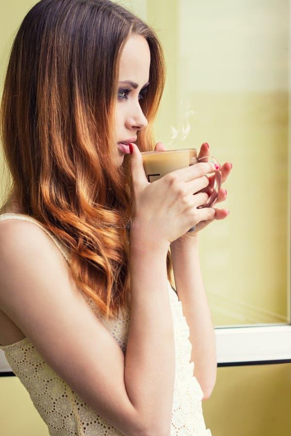 Muchacha hermosa que se coloca en la ventana con una taza caliente de café que vigoriza temprano por la mañana imagen de archivo