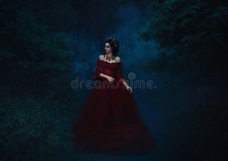 Muchacha hermosa que se coloca en un vestido rojo imagenes de archivo