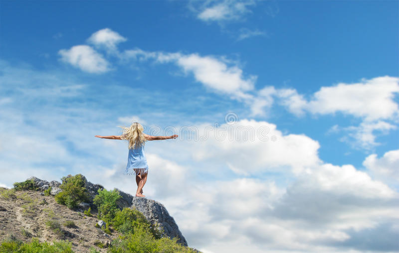 Muchacha hermosa que se coloca en una roca fotografía de archivo libre de regalías