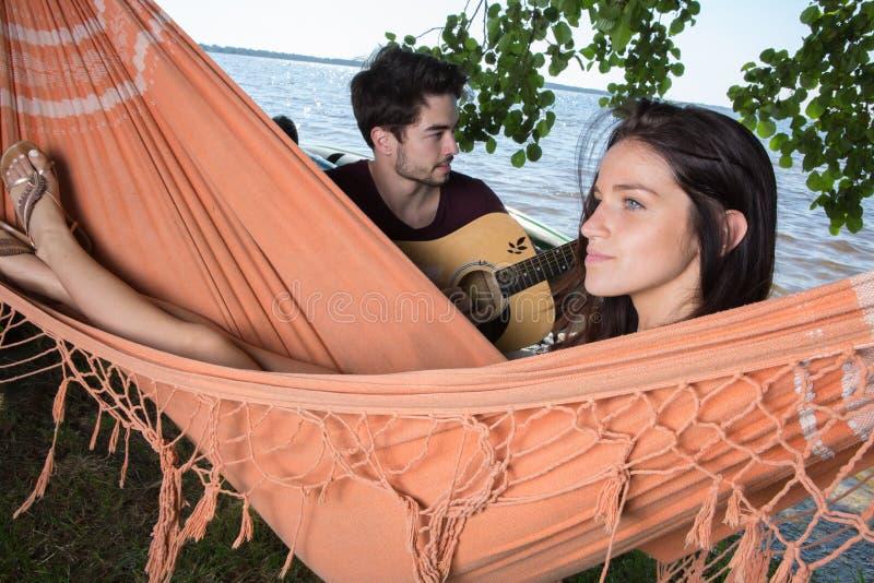 Muchacha hermosa que se relaja en el novio que escucha de la hamaca que toca la guitarra fotografía de archivo libre de regalías
