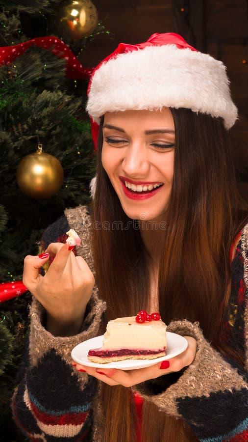 Muchacha hermosa que se sienta cerca de árbol del Año Nuevo y que come la torta deliciosa fotografía de archivo libre de regalías