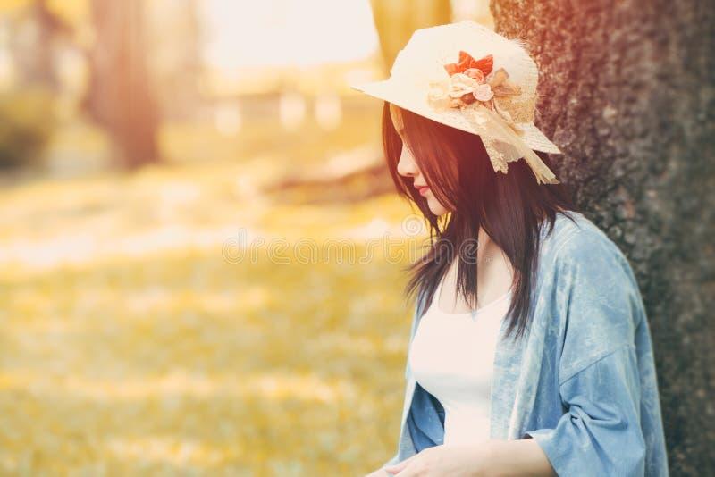 Muchacha hermosa que se sienta debajo del árbol solamente en el parque fotografía de archivo libre de regalías
