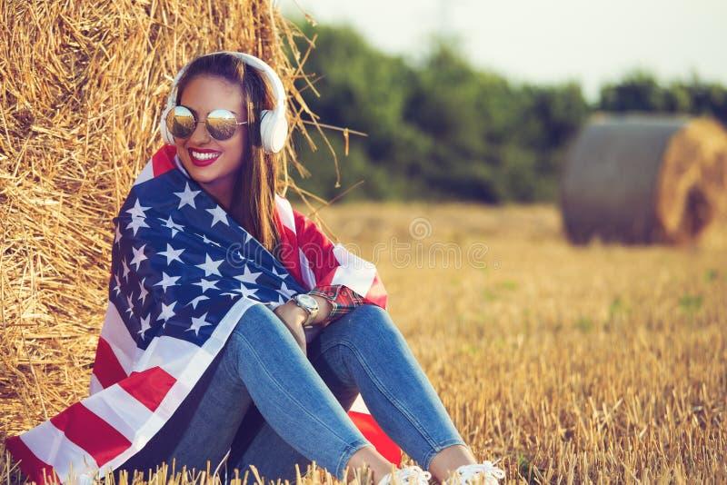Muchacha hermosa que se sienta en el campo, con una bandera de los Estados Unidos de América en sus hombros imagenes de archivo