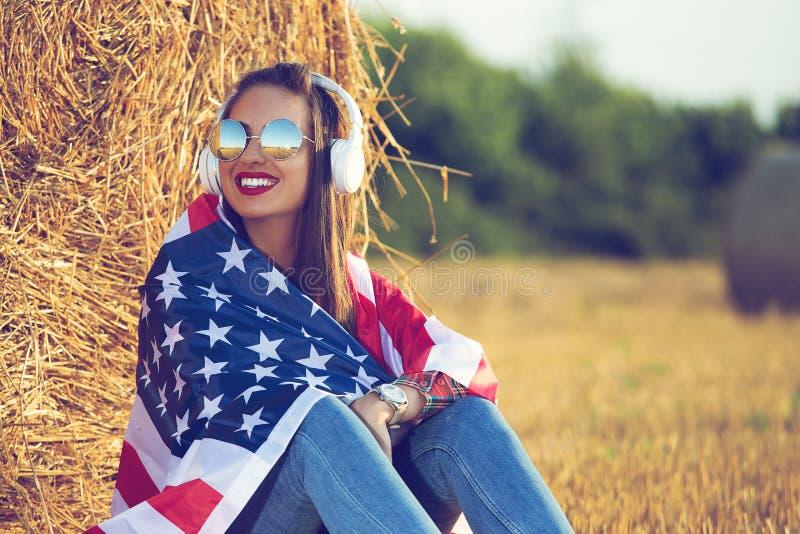 Muchacha hermosa que se sienta en el campo, con una bandera de los Estados Unidos de América en sus hombros imágenes de archivo libres de regalías